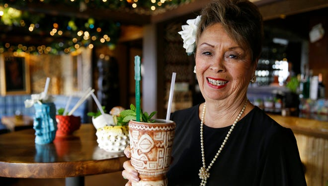In this photo taken Saturday, Dec. 2, 2017, Claudette Lum lifts a Marquesan Drum tiki mug in the lounge at Trader Vic's in Emeryville, Calif. After 57 years as a hostess and maitre d', Lum is retiring at the end of the year.