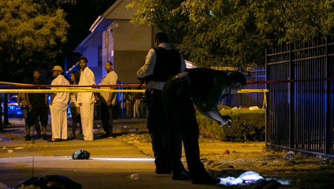 In this Aug. 7, 2016, photo, Chicago police investigate a scene in Chicago where gunfire at a birthday party left a man dead and a woman injured. Police on Monday said they were searching for suspects involved fatal shooting of a 15-year-old boy who was gunned down while assisting his father deliver newspapers.