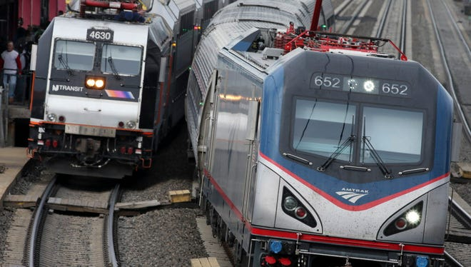 An Amtrak train passes a New Jersey Transit train stopped to discharge and board passengers at Elizabeth train station in Elizabeth, N.J., on March 12, 2016.