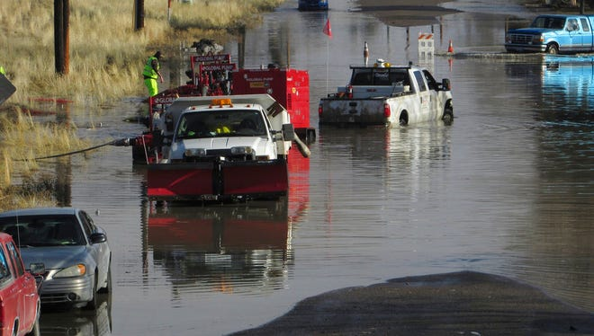In this Feb. 11, 2017, file photo, City of Elko crews pump water from Water Street back into the Humboldt River after the river flooded neighborhoods in both north and south parts of town.