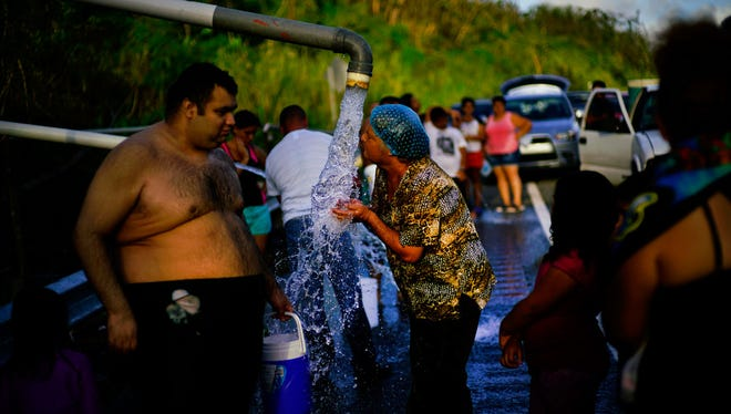 People who lost access to water in the wake of Hurricane Maria gather at pipes carrying water from a mountain creek, on the side of the road in Utuado, Puerto Rico, on Oct. 14.
