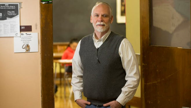John Harvie stands outside a classroom at Riverside High School in Milwaukee where he is a frequent substitute teacher. Harvie, who holds bachelor's degrees in history and political science and a master's in business administration, says better pay and benefits would help Milwaukee Public Schools recruit and retain quality subs.