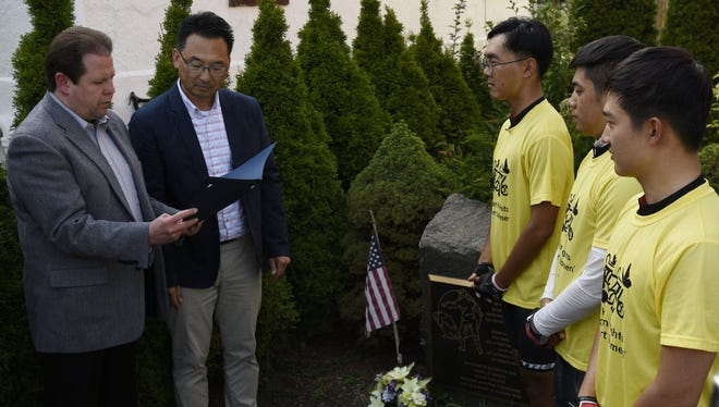 Taewoo Kim, Hankyul Kim and Hyungu Kim, all of South Korea, are presented with a proclamation by Palisades Park Mayor James Rotundo, left, and Councilman Christopher Chung, at the comfort women memorial outside the library, after the three rode their bikes from California to bring awareness to the plight of the comfort women, who were sexually enslaved by the Japanese imperial army before and during World War II.
