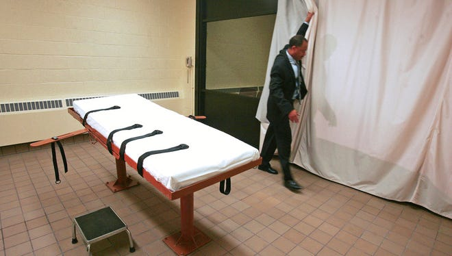 FILE - In this November 2005 file photo, Larry Greene, public information director of the Southern Ohio Correctional Facility, demonstrates how a curtain is pulled between the death chamber and witness room at the prison in Lucasville, Ohio