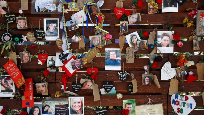 In this Oct. 16, 2017, file photo, photos and notes adorn a wall at the Las Vegas Community Healing Garden in Las Vegas. The garden was built as a memorial for the victims of the recent mass shooting in Las Vegas.