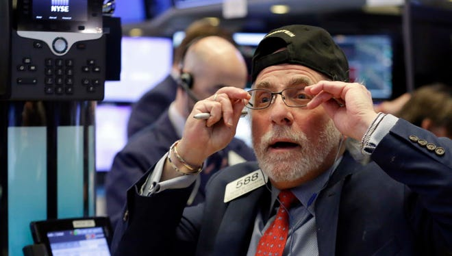 Trader Peter Tuchman works Monday on the floor of the New York Stock Exchange. The Dow Jones industrial average plunged more than 1,100 points Monday as stocks took their worst loss in six and a half years.