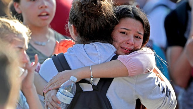 After being released from a lockdown, students embrace in the wake of the Feb. 14, 2018, shooting at Marjory Stoneman Douglas High School in Parkland, Fla.
