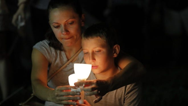 People participate Feb. 19, 2018, in a candlelight vigil in memory of the 17 students and faculty who were killed in the Feb. 14, 2018, mass shooting at Marjory Stoneman Douglas High School in Parkland, Fla.