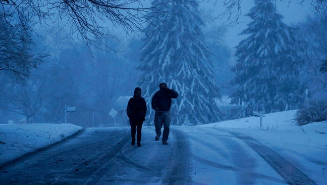 A family walks down a snowy street during a winter storm, Friday, March 2, 2018, in Marple Township, Pa. A nor'easter pounded the Atlantic Coast with hurricane-force winds and sideways rain and snow Friday, flooding streets, grounding flights, stopping trains and leaving 1.6 million customers without power from North Carolina to Maine. At least five people were killed by falling trees or branches. (AP Photo/Matt Slocum)