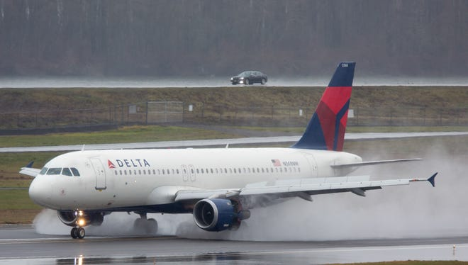A Delta Air Lines Airbus A320 kicks up spray as it lands at Portland (Ore.) International Airport in Oregon in February 2017.