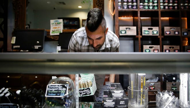 "In this June 27, 2017, file photo, Jerred Kiloh, owner of the Higher Path medical marijuana dispensary, stocks shelves with with cannabis products in Los Angeles. State regulators have warned the popular website Weedmaps to take down ads from illegal sellers or face possible penalties, but the company says it's not breaking any laws. Kiloh said ""That's Weedmaps' business model, to confuse the difference between legal and illegal,"" Kiloh, a licensed dispensary owner who heads the United Cannabis Business Association, an industry group."