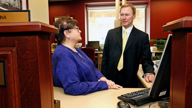 WaterStone Bank CEO Doug Gordon talks with bank teller Donna Agnelly at the bank's Waukesha branch.