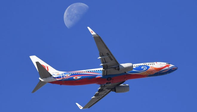 An Air China plane flies in front of the moon as it takes off from Beijing airport on November 10, 2017.