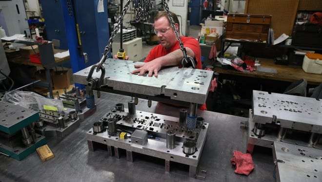Justin Schmeling, a tool-and-die maker, does maintenance on stamping tooling at Wisconsin Metal Parts Inc. in Waukesha.