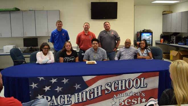 Pace High football's Malik Perez signs with Cincinnati Christian University joined by (front row L to R) sister Trinity Perez, mom Jessica Perez, Malik Perez, dad Jose Perez, sister Aliyah Perez (back row L to R)  Head Coach Kent Smith, Assistant Principal Dustan Gray, assistant coach Bill Jernigan.