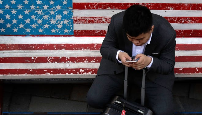 In this April 10, 2018, photo, a man on a bench with an American flag checks his smartphone in Beijing. The Asian Development Bank is forecasting that developing Asian economies will expand at a slightly faster pace this year than earlier expected, but U.S. trade tensions pose a major risk.