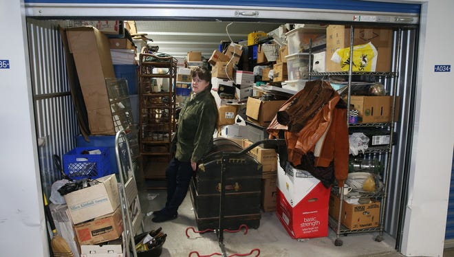 Alice Donohoe, who downsized from a large Glendale home after raising her 10 children, looks over the items in her 40-foot by 10-foot storage unit at U.S. Storage Depot, 4200 N. Holton St. Donohoe started three years ago with four units, but has given away much of what she stored in them. She now rents one unit, which holds family keepsakes she plans to give to her children.