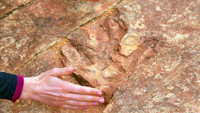 This undated photo provided by the Utah Division of Parks and Recreation shows visitors examining dinosaur tracks at the Red Fleet State Park east of Salt Lake City. The site, lined with hundreds of prehistoric raptor tracks, has been heavily damaged in the past six months. Visitors have been dislodging dinosaur tracks imprinted in sandstone and throwing the pieces into a nearby lake, officials said.