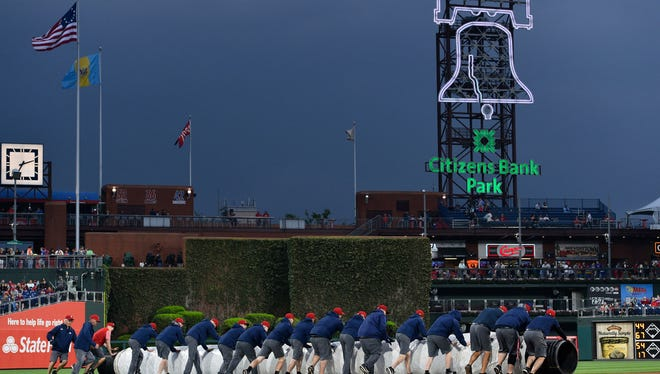 Grounds crews roll the tarp on to the field prior to a baseball game between the Philadelphia Phillies and the New York Mets as heavy storms were anticipated, Saturday, May 12, 2018, in Philadelphia.