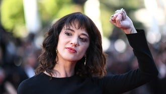 Actress Asia Argento raises her fist as she arrives Saturday for the closing ceremony. She took the awards stage to give a blistering speech about Harvey Weinstein, the disgraced movie mogul she's accused of raping her at Cannes.