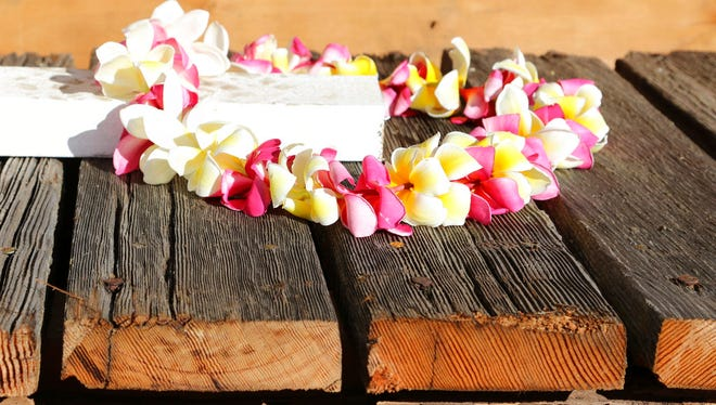 A flower lei sits on part of a wood deck from the USS Arizona, which is being held in place by white beams as it sits in a crate while waiting to be loaded onto an airplane June 21, 2018, in Honolulu. An 800-pound chunk from the USS Arizona battleship that sank during the Japanese bombing of Pearl Harbor is heading to Texas for display at a war memorial.