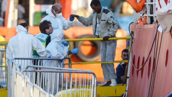 """Migrants are helped off the """"MV Lifeline,"""" a German humanitarian ship, as it arrives in Malta on June 27, 2018."""
