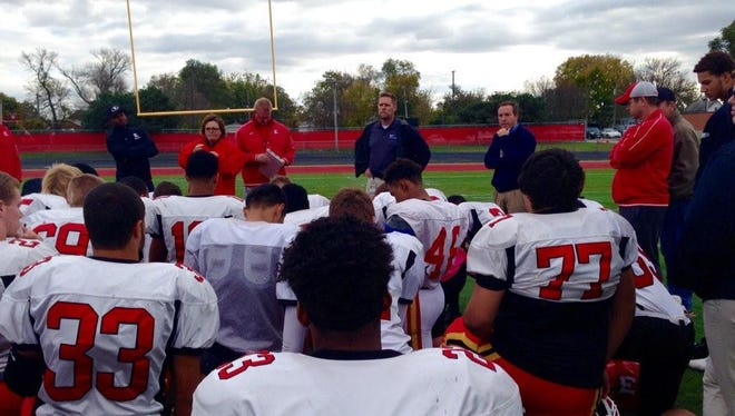 Des Moines schools Superintendent Tom Ahart, center with hands on hips, tells Des Moines East High School football players Friday afternoon at Williams Stadium that East would forfeit a scheduled game that night after being told it could not be played in Des Moines.