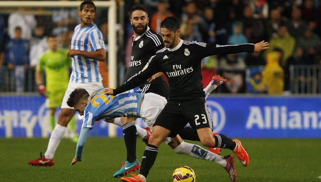 Real Madrid's Isco (R) controls the ball during their Spanish First Division soccer match against Malaga at La Rosaleda stadium in Malaga, southern Spain Nov. 29, 2014.