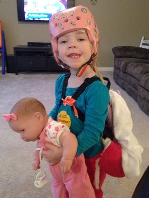 Addyson Benton, 2, normally wears a pink helmet covered in stickers to prevent her from any injury she might endure from the multiple seizures she has during the day.