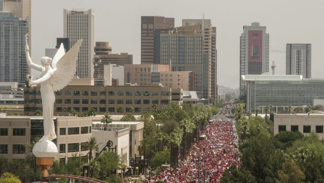 Parents, students, and educators supporting #RedForEd walks towards the Arizona State Capitol on April 26, 2018
