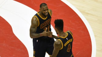 Cleveland Cavaliers forward LeBron James (23) reacts with guard Iman Shumpert (4) during the second quarter in game two of the Eastern Conference Finals of the NBA Playoffs against the Atlanta Hawks at Philips Arena. Mandatory Credit: Dale Zanine-USA TODAY Sports