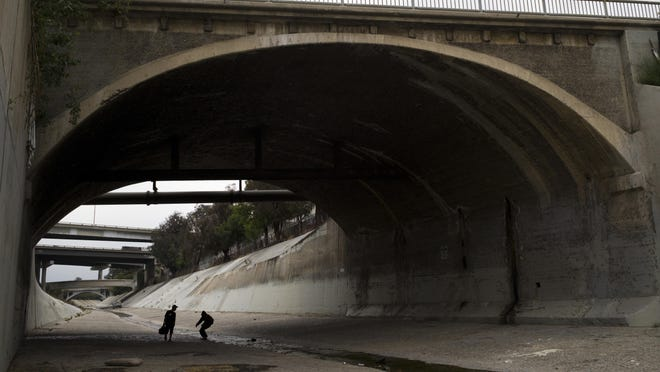 Two homeless men walk under the bridge along the Los Angeles River in Los Angeles, where almost extinct form of American hieroglyphics known as hobo graffiti were discovered.