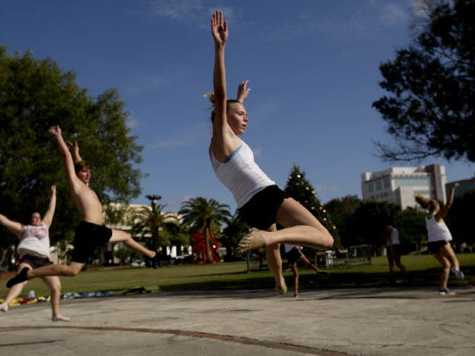 From front to back, Madalynn Warnken, 16, Michael Haefele, 16, and Aireal Golladay, 18, practices with the color guard unit as part of the group called Mercata at Centennial Park in Fort Myers on Thursday 1/2/2014.  They are an independent group of students aged 13-23 who participate in competitions throughout the state.   They are affiliated with the drum line group called Marcato.