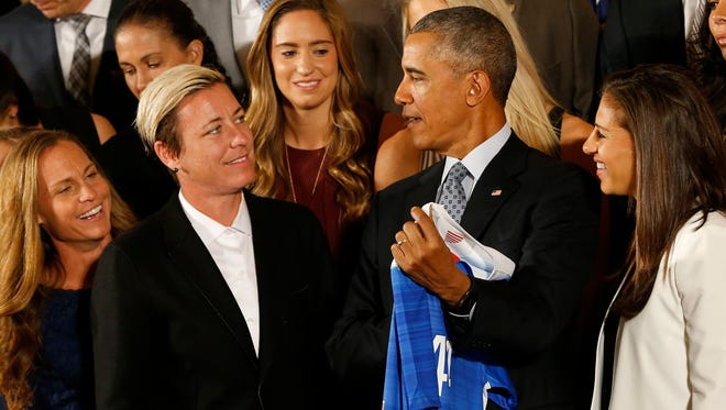 President Barack Obama  holds an honorary team jersey while talking with Team USA forward Abby Wambach (L) and midfielder Carli Lloyd (R) on Oct. 27, 2015.