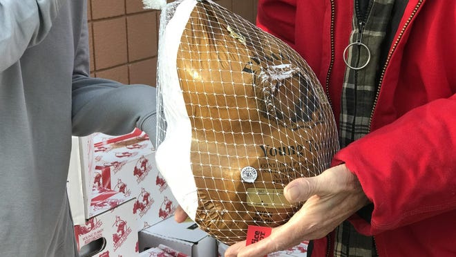 A guest picks up a turkey from Community Action House during Thanksgiving in 2019.