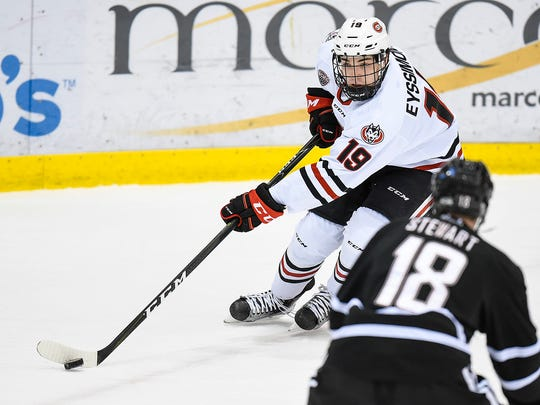 St. Cloud State's Mikey Eyssimont takes the puck past Nebraska-Omaha's Dean Stewart during the first period Friday, Dec. 9, Herb Brooks National Hockey Center.