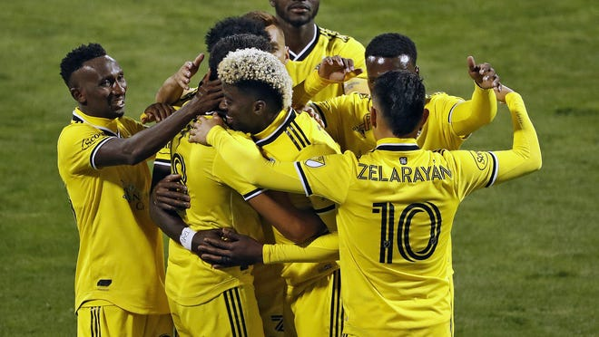 Forward Gyasi Zardes, center, is mobbed by teammates after scoring in stoppage time on Saturday night at Mapfre Stadium to give the Crew a two-goal advantage against Nashville SC.