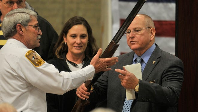 Autauga County chief deputy and sheriff-elect Joe Sedinger, left, hands retiring Sheriff Herbie Johnson a Browning 12 ga. over and under shotgun on Thursday, Jan. 15, 2015, at Johnson's retirement party at the Doster Memorial Community Center in Prattville.
