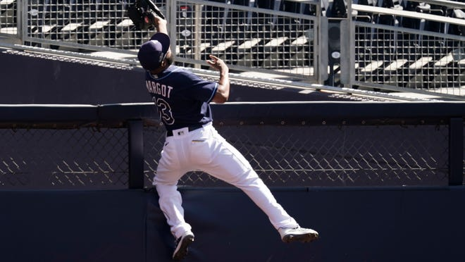 Tampa Bay Rays right fielder Manuel Margot reaches over a right field wall after catching a foul ball by Houston Astros center fielder George Springer during the second inning in Game 2 of a baseball American League Championship Series, Monday, Oct. 12, 2020, in San Diego.