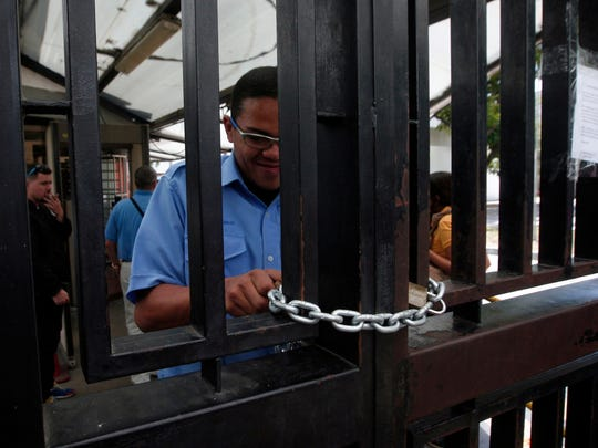 A Kellogg's security officer chains the main door shut at the company's factory in Maracay, Venezuela, Tuesday, May 15, 2018. Workers arriving Tuesday for the early shift were surprised to find a notice taped to the iron gate informing them that the company had been forced to shutter its operations. (AP Photo/Juan Carlos Hernandez)