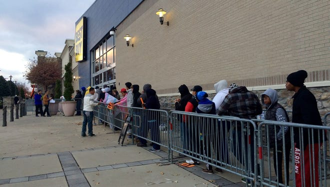 Dozens of people line up outside Best Buy on Thanksgiving for early Friday deals.