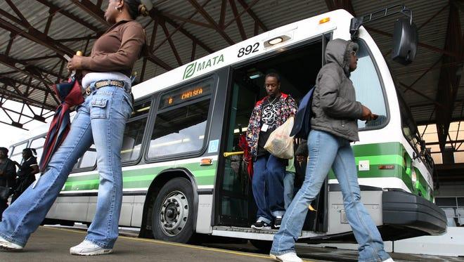Morning bus riders change busses at the north terminal at 444 North Main.