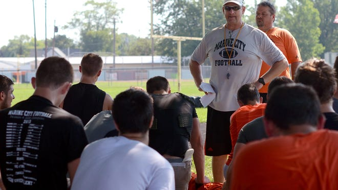 Coach Ron Glodich addresses his team about managing fatigue Monday, Aug 17, after football practice at Marine City High School.