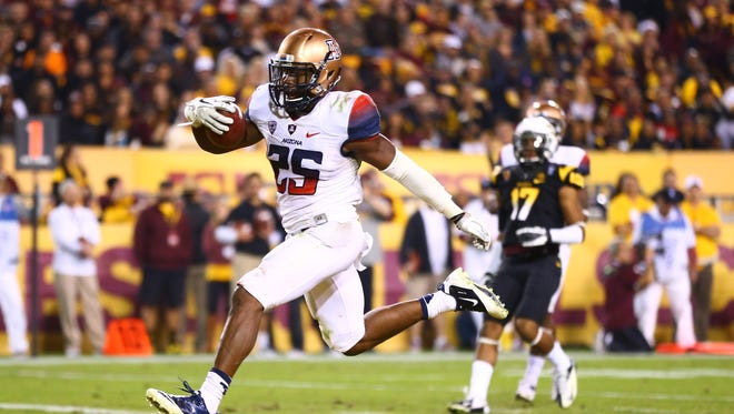 Arizona Wildcats running back Ka'Deem Carey (25) scores a touchdown in the second half against the Arizona State Sun Devils in the 87th annual Territorial Cup at Sun Devil Stadium. Arizona State defeated Arizona 58-21.