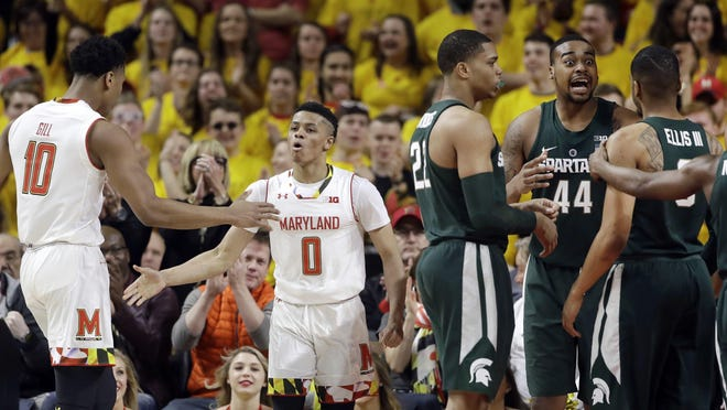 Maryland guard Anthony Cowan (0) high-fives teammate L.G. Gill after Cowan was fouled in the first half against Michigan State on Saturday, March 4, 2017 in College Park, Md.