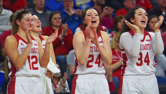 USD's Jaycee Bradley (12),  Ciara Duffy (24) and Kate Liveringhouse (34) cheer for their team during the game against Fort Wayne Saturday, March 3, during the Summit League basketball tournament at the Denny Sanford Premiere Center in Sioux Falls.