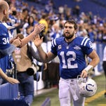 Indianapolis Colts quarterback Andrew Luck slaps hand with his fans after he and his teammates made their way around the stadium showing their appreciation, December 29, 2013.