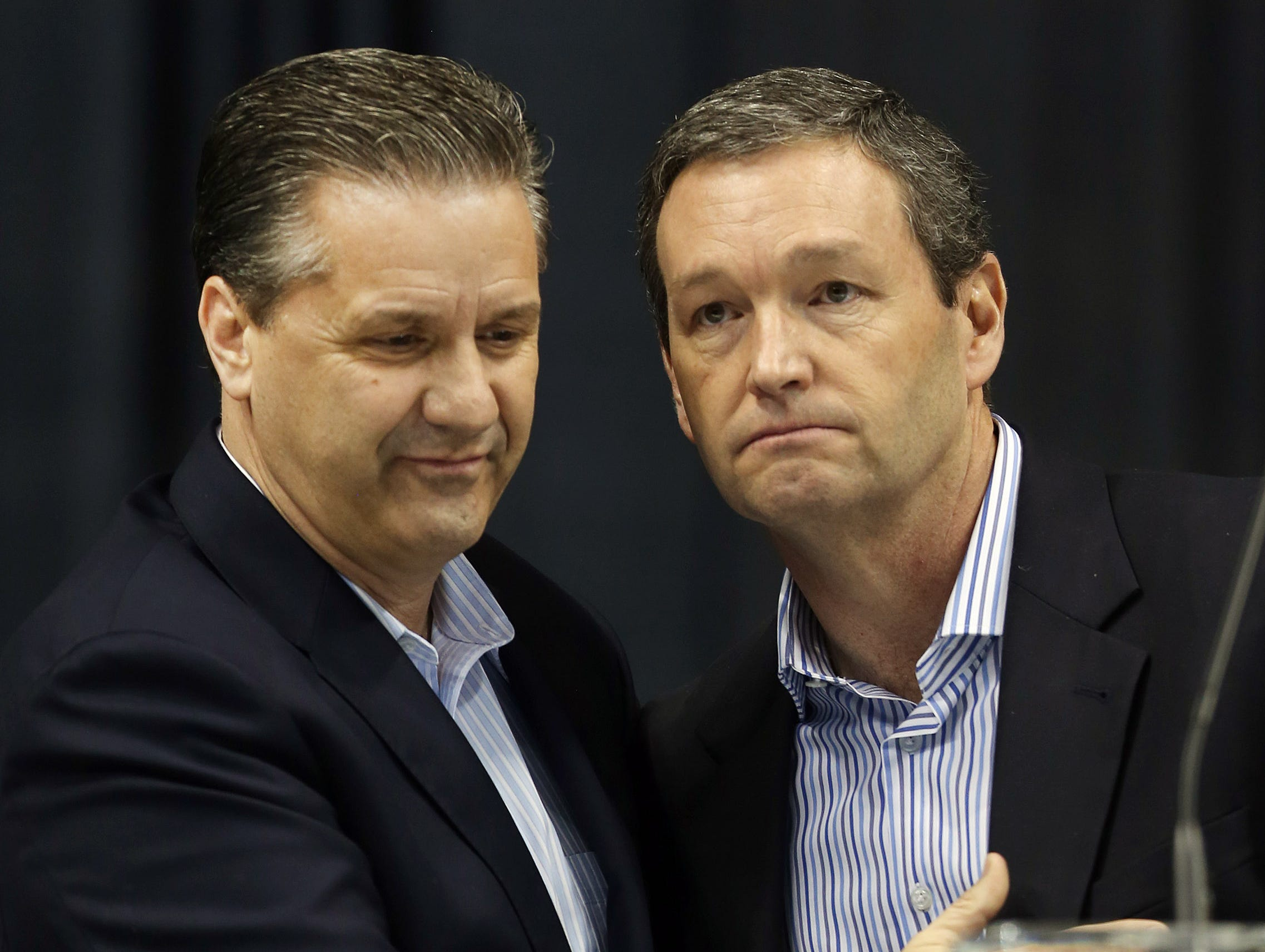 Kentucky head coach John Calipari, left, is introduced by Athletics Director Mitch Barnhart during a celebration of Kentucky's run in the 2014 NCAA Tournament at Rupp Arena in Lexington. April 8, 2014