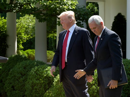 Vice President Mike Pence, right, takes his seat after introducing President Donald Trump in the Rose Garden of the White House in Washington, Thursday, June 1, 2017, to announce that the U.S. will withdraw from the Paris climate change accord.