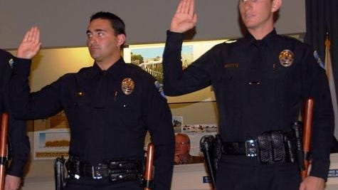 Palm Springs police officers Michael Heron, left, and Chad Nordman are sworn in during a City Council meeting.
